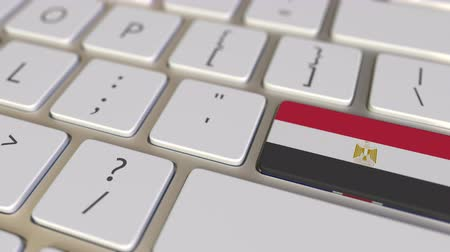 immigrazione : Key with flag of Egypt on the computer keyboard switches to key with flag of Great Britain, translation or relocation related animation