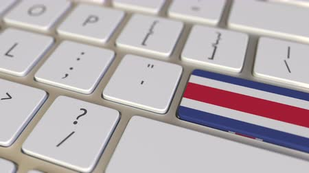 traduire : Key with flag of Costa Rica on the computer keyboard switches to key with flag of Great Britain, translation or relocation related animation Vidéos Libres De Droits