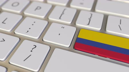 traduire : Key with flag of Colombia on the computer keyboard switches to key with flag of Great Britain, translation or relocation related animation