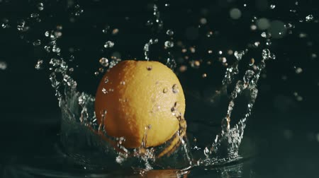 wetness : Orange falls on shallow water surface. Slow motion, shot on Red