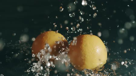 wetness : Two oranges fall on shallow water surface. Slow motion, shot on Red Stock Footage