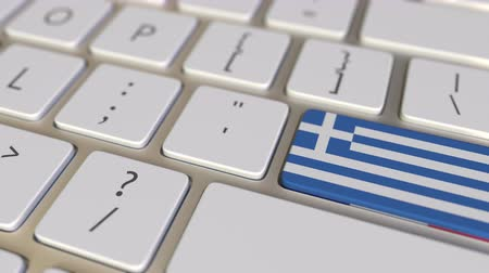 иммиграция : Key with flag of Greece on the computer keyboard switches to key with flag of France, translation or relocation related animation