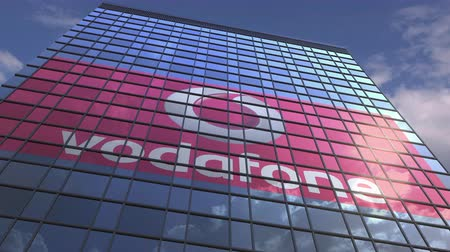 oficial : VODAFONE logo against modern building reflecting sky and clouds, editorial animation