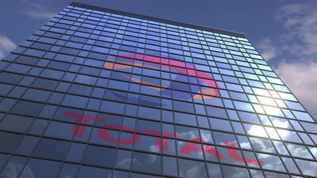 celkový : TOTAL logo on modern building reflecting sky and clouds, editorial animation