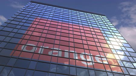 zrcadlící : Logo of ORANGE on a media facade with reflecting cloudy sky, editorial animation