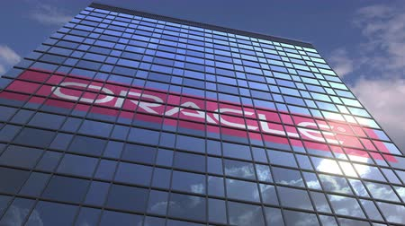 odrážející : Logo of ORACLE on a media facade with reflecting cloudy sky, editorial animation
