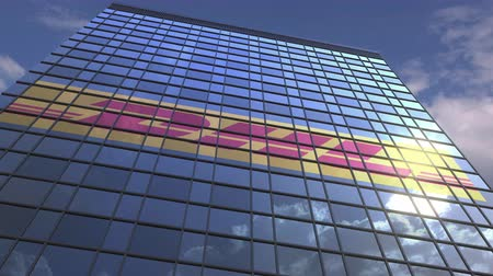odrážející : Logo of DHL on a media facade with reflecting cloudy sky, editorial animation