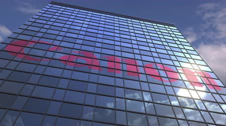 canon : CANON logo against modern building reflecting sky and clouds, editorial animation Stock Footage