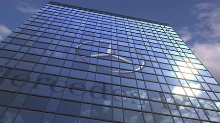 oficial : MERCEDES-BENZ logo against modern building reflecting sky and clouds, editorial animation