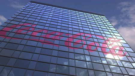 kola : Logo of COCA-COLA on a media facade with reflecting cloudy sky, editorial animation