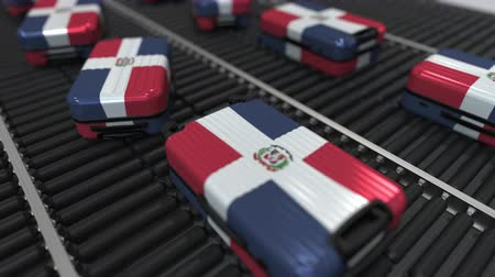 emigrazione : Many travel suitcases featuring flag of the Dominican Republic on roller conveyer. Tourism related conceptual animation