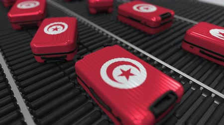 tunus : Many travel suitcases featuring flag of Tunisia on roller conveyer. Tunisian tourism conceptual animation Stok Video