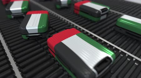 handling : Many travel suitcases featuring flag of the United Arab Emirates on roller conveyer. UAE tourism conceptual animation