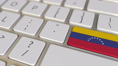 immigratie : Key with flag of Venezuela on the keyboard switches to key with flag of Germany, translation or relocation related animation Stockvideo