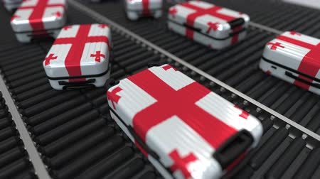 emigrazione : Many travel suitcases featuring flag of Georgia on roller conveyer. Georgian tourism conceptual animation