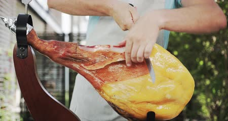 вылеченный : Unknown man cutting the whole jamon leg, a type of dry-cured ham from Spain. Shot on Red