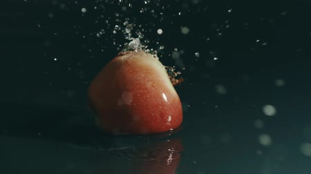 slomo : Single red apple splashes in shallow water. Slow motion, shot on Red