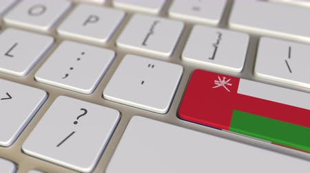működés : Key with flag of Oman on the keyboard switches to key with flag of France, translation or relocation related animation Stock mozgókép