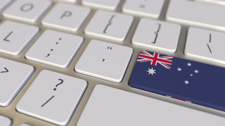 immigratie : Key with flag of Australia on the computer keyboard switches to key with flag of Great Britain, cooperation or relocation related animation