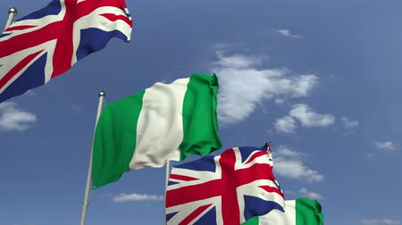nigeria flag : Flags of Nigeria and the United Kingdom against blue sky, loopable 3D animation