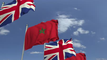 марокканский : Waving flags of Morocco and the United Kingdom on sky background, loopable 3D animation Стоковые видеозаписи