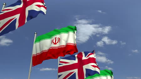 onderhandeling : Waving flags of Iran and the United Kingdom on sky background, loopable 3D animation Stockvideo