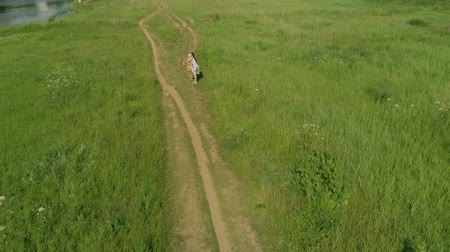 река : Aerial view of mom and her little child hugging on rural pathway