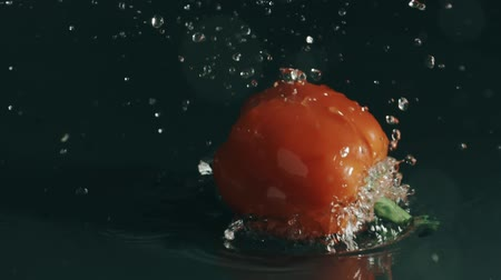 ピーマン : Bell pepper splashes in shallow water. Slow motion shot on Red