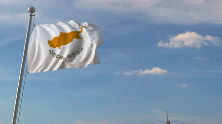 megérkezik : Airliner passing above national flag of Cyprus. Cypriot air transportation related 3D animation Stock mozgókép