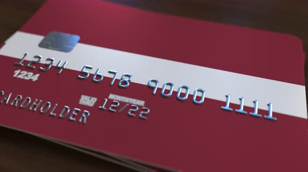 debit : Plastic bank card featuring flag of Latvia. Latvian national banking system related animation Stock Footage