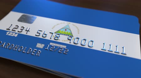 debit : Plastic bank card featuring flag of Nicaragua. Nicaraguan national banking system related animation Stock Footage