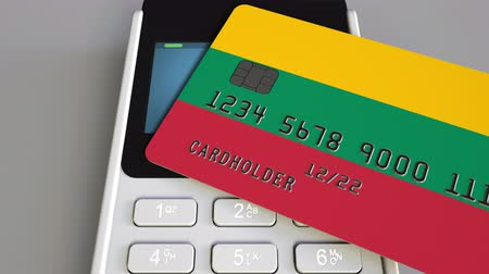 flag of lithuania : Plastic bank card featuring flag of Lithuania and POS payment terminal. Lithuanian banking system or retail related 3D animation