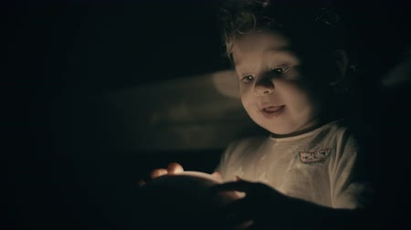 освещенный : Happy little baby looks at luminous projecting toy in dark room
