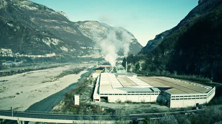 itália : Aerial shot of air polluting plant in the river valley in northern Italy
