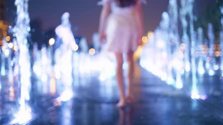 nemli : Beautiful young woman wearing dress walks in the illuminated fountain in the evening, slow motion