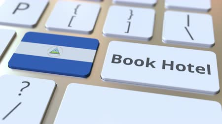 nicaraguan : BOOK HOTEL text and flag of Nicaragua on the buttons on the computer keyboard. Travel related conceptual 3D animation Stock Footage