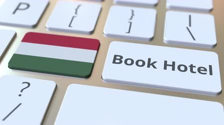 horeca : BOOK HOTEL text and flag of Hungary on the buttons on the computer keyboard. Travel related conceptual 3D animation Stock Footage