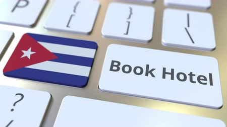 vendég : BOOK HOTEL text and flag of Cuba on the buttons on the computer keyboard. Travel related conceptual 3D animation