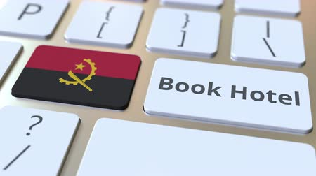 vendégszeretet : BOOK HOTEL text and flag of Angola on the buttons on the computer keyboard. Travel related conceptual 3D animation