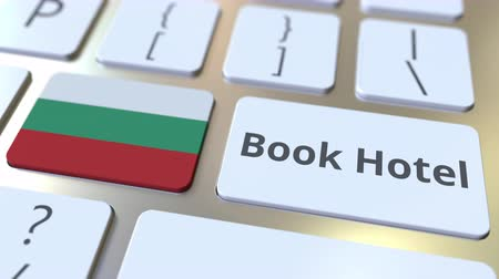 bolgár : BOOK HOTEL text and flag of Bulgaria on the buttons on the computer keyboard. Travel related conceptual 3D animation Stock mozgókép