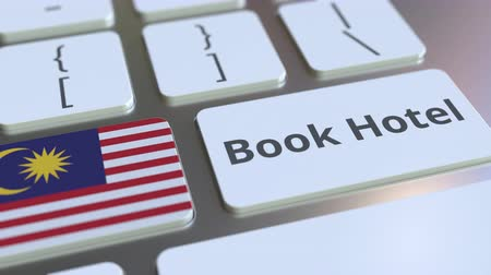 convidado : BOOK HOTEL text and flag of Malaysia on the buttons on the computer keyboard. Travel related conceptual 3D animation