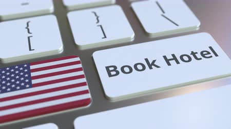 külföldi : BOOK HOTEL text and flag of the United States on the buttons on the computer keyboard. Travel related conceptual 3D animation Stock mozgókép