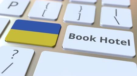 yabancı : BOOK HOTEL text and flag of Ukraine on the buttons on the computer keyboard. Travel related conceptual 3D animation