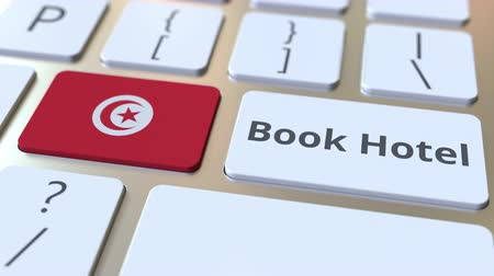гостеприимство : BOOK HOTEL text and flag of Tunisia on the buttons on the computer keyboard. Travel related conceptual 3D animation Стоковые видеозаписи