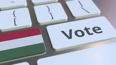 demokratický : VOTE text and flag of Hungary on the buttons on the computer keyboard. Election related conceptual 3D animation
