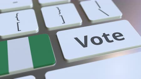demokratický : VOTE text and flag of Nigeria on the buttons on the computer keyboard. Election related conceptual 3D animation