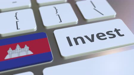 assets : INVEST text and flag of Cambodia on the buttons on the computer keyboard. Business related conceptual 3D animation Stock Footage