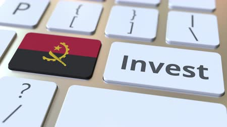 bens : INVEST text and flag of Angola on the buttons on the computer keyboard. Business related conceptual 3D animation Stock Footage