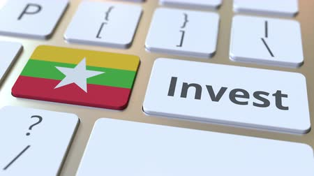 mianmar : INVEST text and flag of Myanmar on the buttons on the computer keyboard. Business related conceptual 3D animation Stock Footage