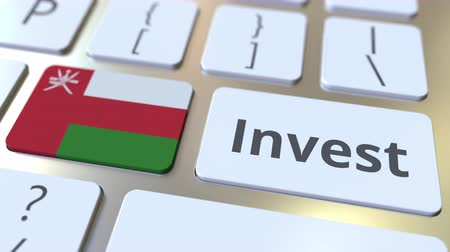 bens : INVEST text and flag of Oman on the buttons on the computer keyboard. Business related conceptual 3D animation Stock Footage